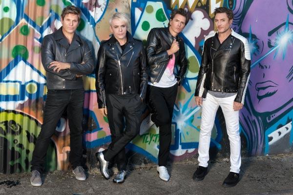 Duran Duran band members standing next to graffiti back2back productions