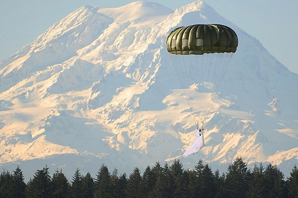 Bride parachuting into her wedding in front of a mountain range