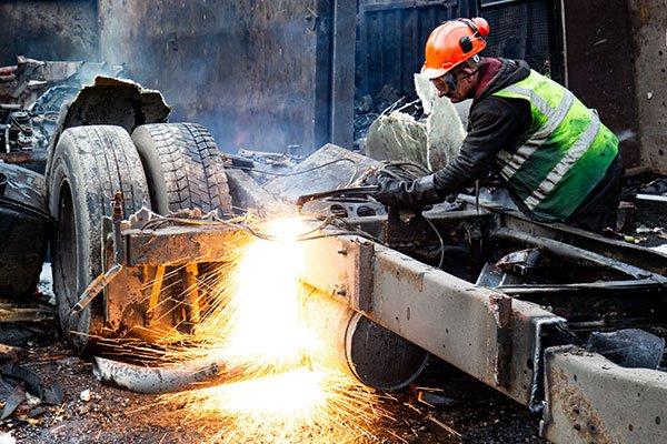 Man cutting metal in Scrap Kings-back2back productions