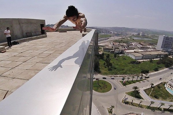Lady completing daring trick on the edge of a building back2back productions
