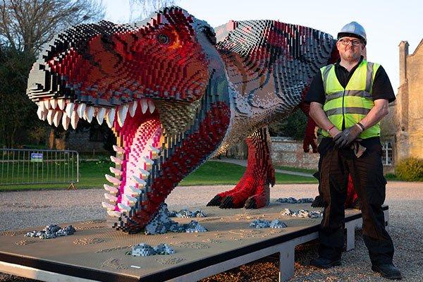 Man moving large model dinosaur back2back productions