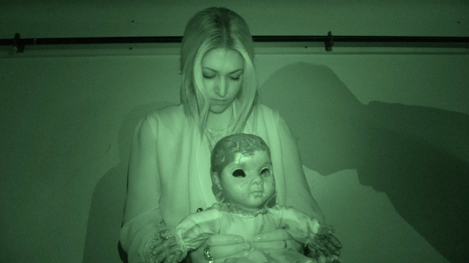 Night vision shot of a giral and doll with ghostly shadows behind them