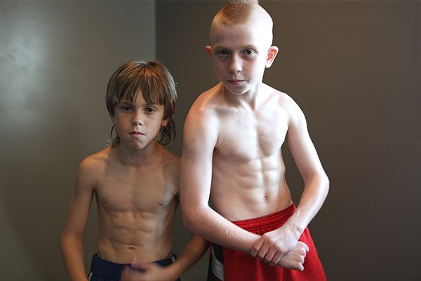 Two youg body builder boys flexing their muscles