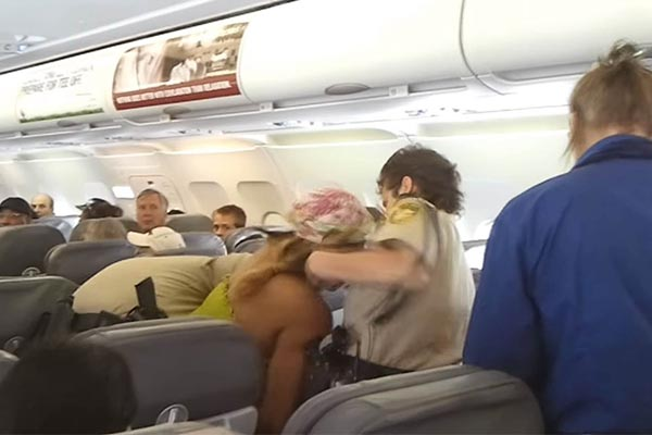 Woman being extracted from a plane by Police