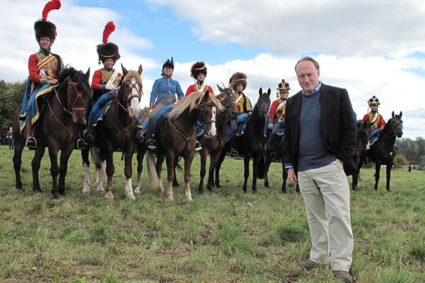 Historian Andrew Roberts at a battle re enactment standing in fromt of mounted horseriders