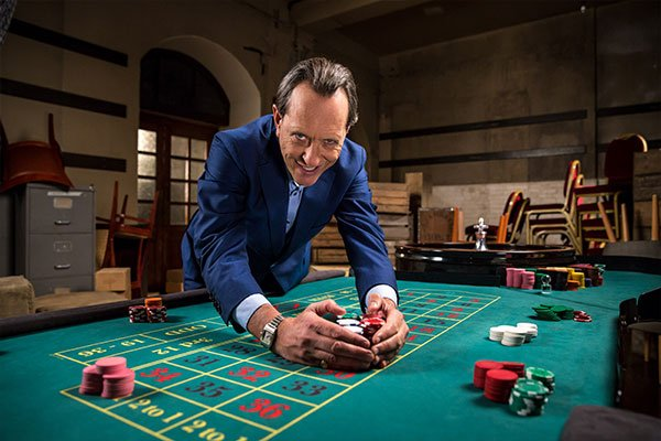 Richard E Grant leaning over a poker table