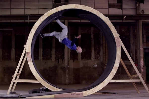 Person rinning around in a giant mouse wheel